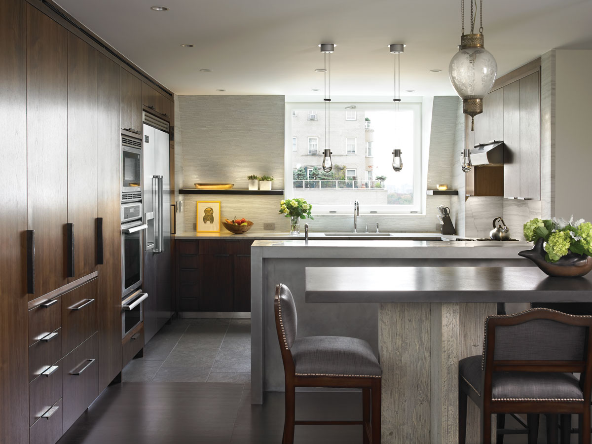 In the kitchen, a dated copper wall was knocked down to open up the space. A zinc bar blends seamlessly with the gray limestone flooring from Stone Source. The clients introduced pendants from their previous dwelling to add a warm, sentimental note.
