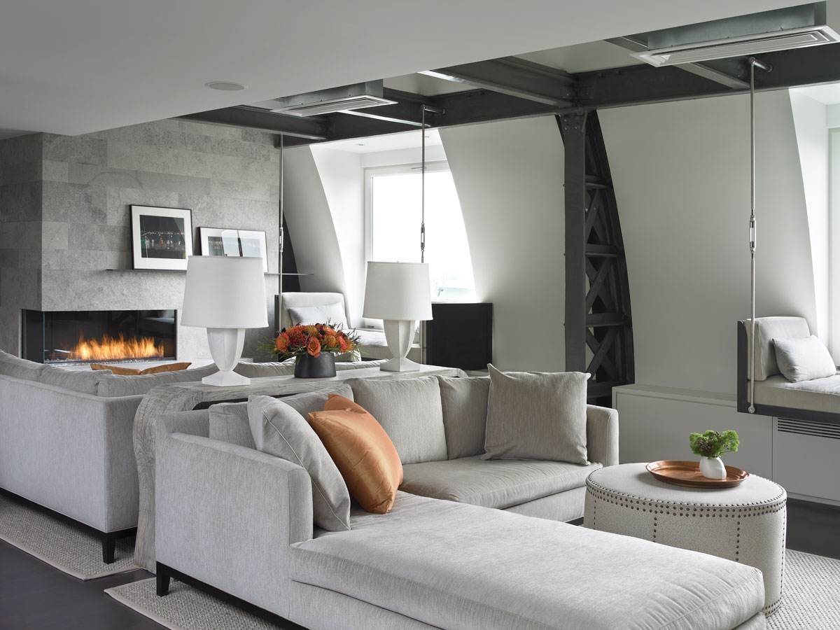 Scott created two seating areas in the living room with sofas positioned back to back. A Clubcu console table separates them while shapely limestone lamps from Oly Studio add a sophisticated note.