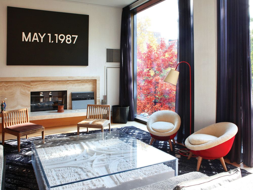 "Works by two Japanese artists—On Kawara above the fireplace and Yutaka Sone's marble sculpture of a Los Angeles freeway interchange-turned coffee table—grace the living room, which also boasts  Royère ""Oeuf"" chairs and a custom V'Soske rug."