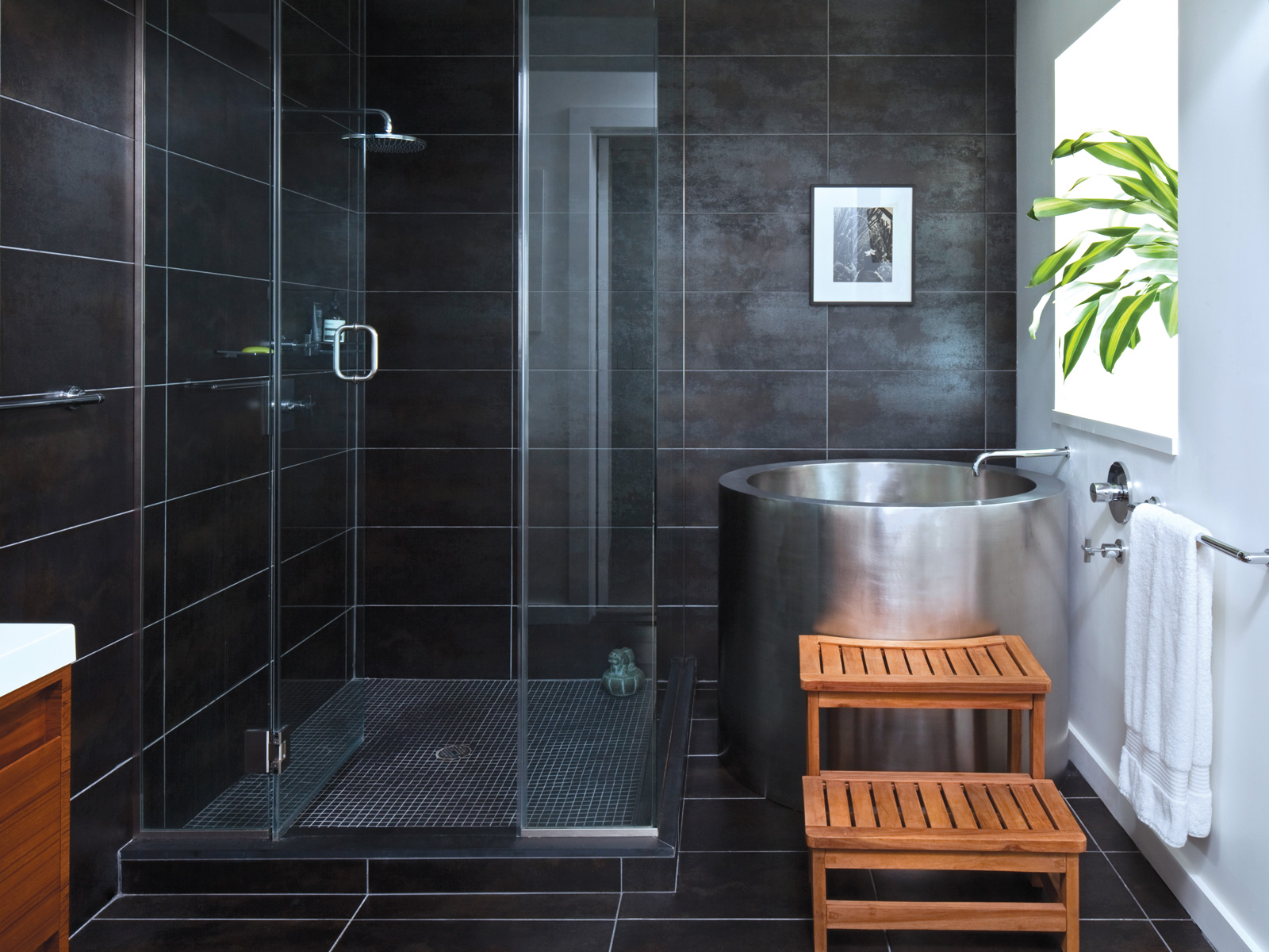 A Japanese soaking tub pops against dark slate tiles in the master bath.