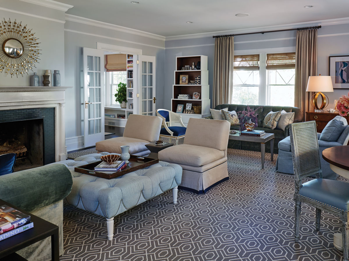 The living room's refined aesthetic was achieved without extravagance by relying on practically priced fabrics (the custom sofas' Fabricut cotton velvet, various Schumacher linens on the curtains, ottoman and slipper chairs) and carefully selected rack pieces from Hickory Chair (cocktail table, Le Clerc side chair), Bungalow 5 (tall display case), and Arteriors (mirror).