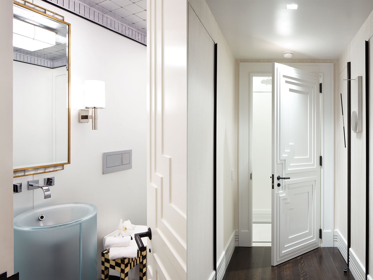 Left: In the powder room, a Dornbracht faucet empties into a Vitraform sink below a Paul Stamati mirror. Right: A black-and-white Jesús Soto work hangs by a custom-designed door.