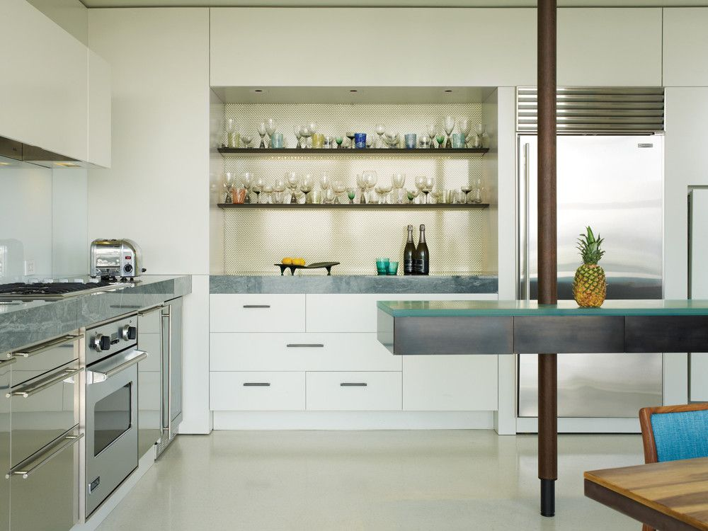 To create more storage and redirect the energy away from the windows, In Situ created an aluminum honeycomb backsplash sandwiched between acrylic panels that are lit from behind. The floating kitchen island is topped in a cast blue resin with a silver-leafed underside that yields a water-like appearance and relates to the aquatic environment outside.