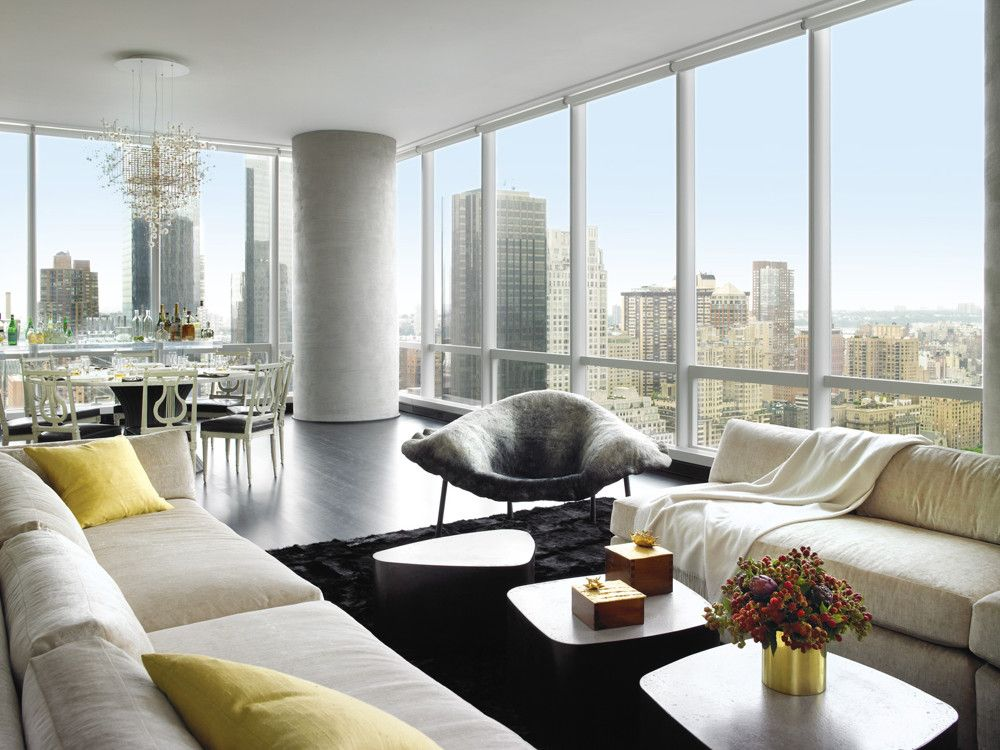 The vast great room divided easily into living and dining areas focused on the spectacular view. To create the effect of a curtain without blocking the vistas, Mann draped the interior wall as a backdrop for two  facing custom sofas in Fabricut velvet. The custom Galet tables by Stephane Ducatteau are from Decoratum; Ayala Serfaty's armchair from Maison Gerard; the Arbre á Bulles brass 
