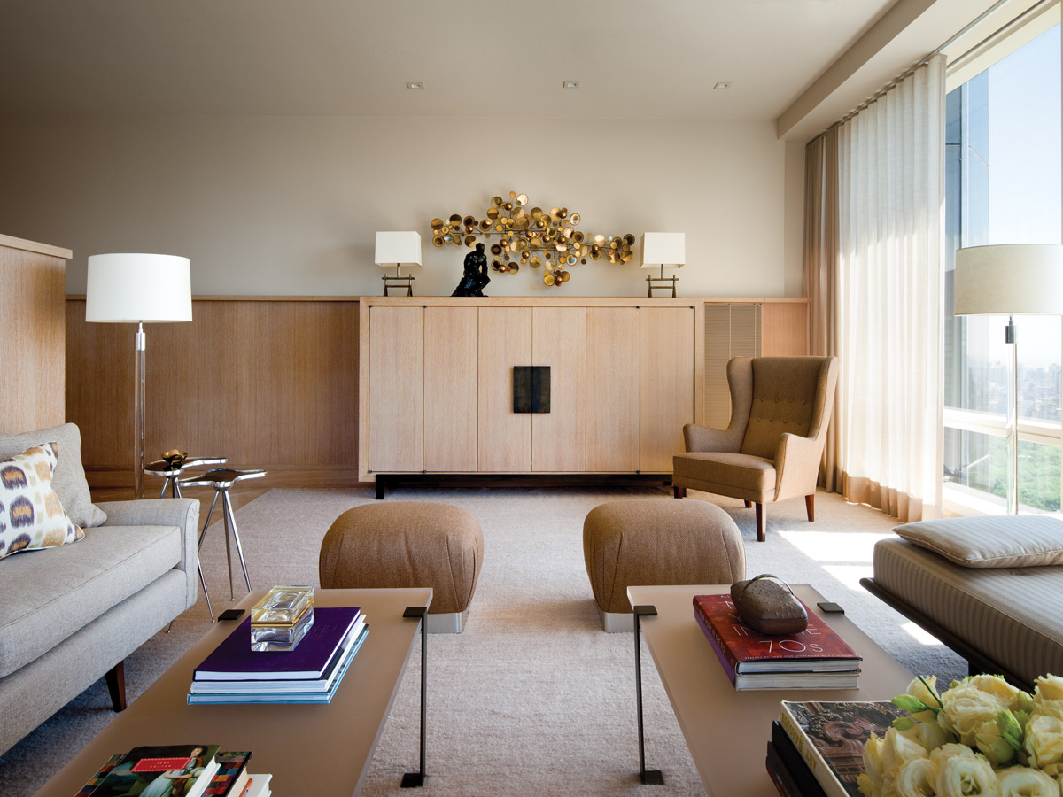 At one end of the living room, a mid-century wing chair from Arenskjold Antiques sits by a custom TV cabinet.