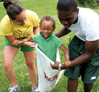 Summer Spot camp counselors Samantha Chin and Ronald Simpson help 7-year-old Izick Maclin in the sack race.