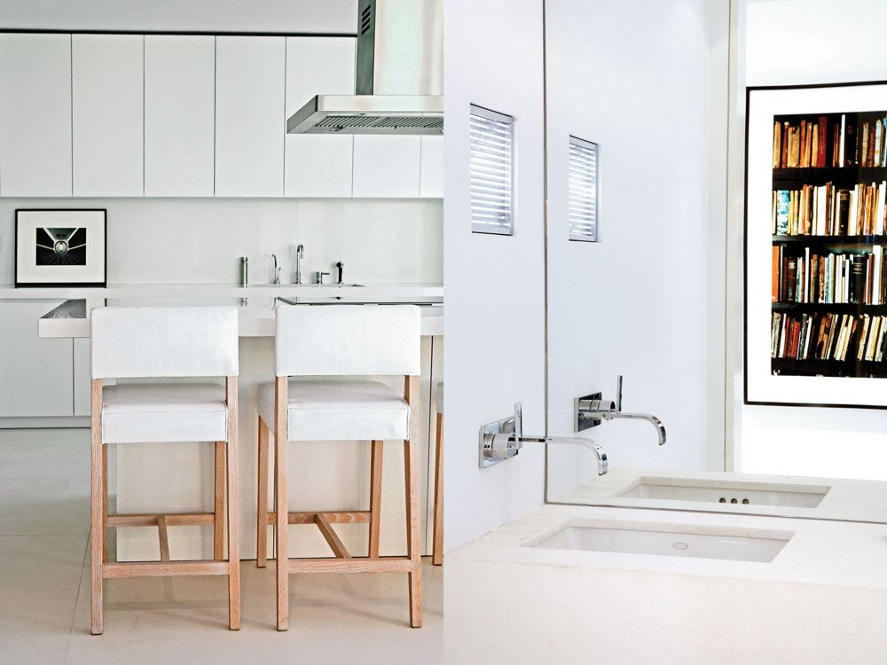 Left: In the sleek, white kitchen, custom Christophe Pourny stools pull up to the counter opposite a photo by Ruth Barnard. Right: In the powder room, a light sculpture by Leo Villareal is cleverly paired with a photograph by Andrew Moore; the faucet is from Dornbracht.