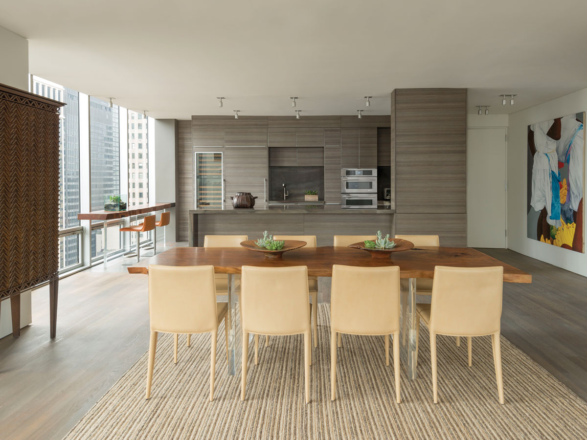 The handcrafted dining table from Hudson Furniture sits atop a rug by English designer Rosemary Hallgarten. Dining chairs from Suite NY complete the setting. The couple's Cor-Ten steel armoire, which they brought from Colombia, graces the head of the table. The painting is by Colombian artist Ana Mercedes Hoyos.