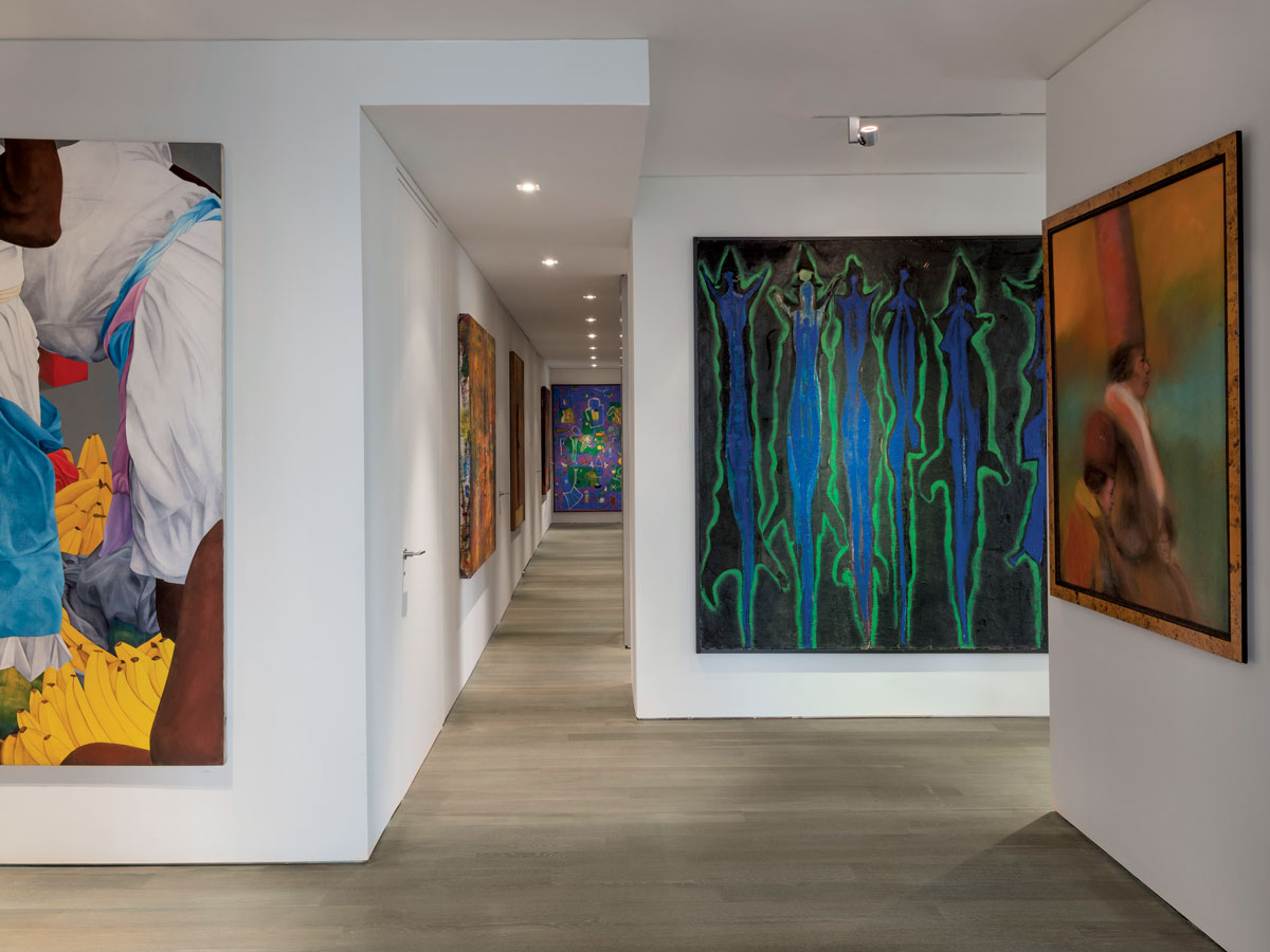 The owner's collection of modern South American art adds a strong personal touch. At left is a painting by Ana Mercedes Hoyos; right, a Ruben Leyva. Art by Sergio Hernandez is at the hallway's end and a work by Santiago Cardenas is on the right-hand column.