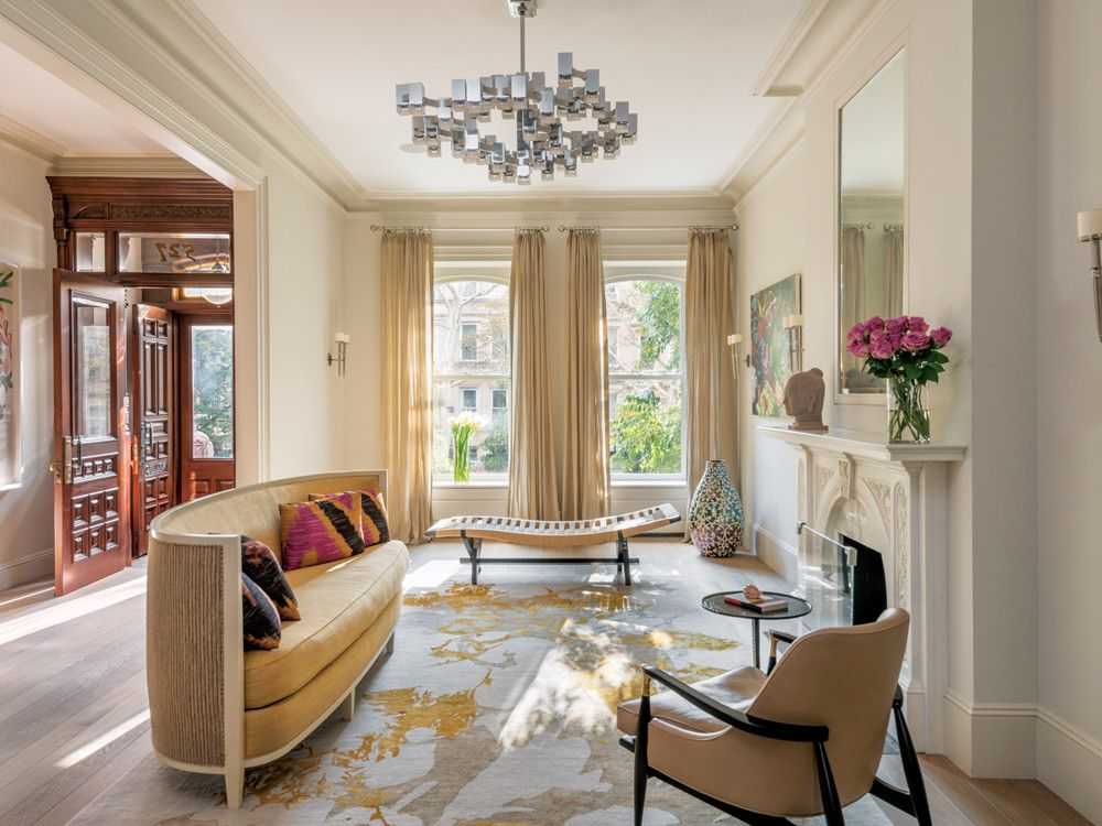 In the living room, the architects widened the hallway entrance to bring in more light while retaining the original wood paneling. Fogarty Finger's interior design team created a custom rug to highlight the elegant Andrée Putman Crescent Moon sofa by Ralph Pucci. The large Gaetano Sciolari  chandelier masterfully dominates the space. A vintage Henry Klumb chaise from Mondo Cane lends an artful grace note and a wood and bronze side chair from J. F. Chen provides additional seating.