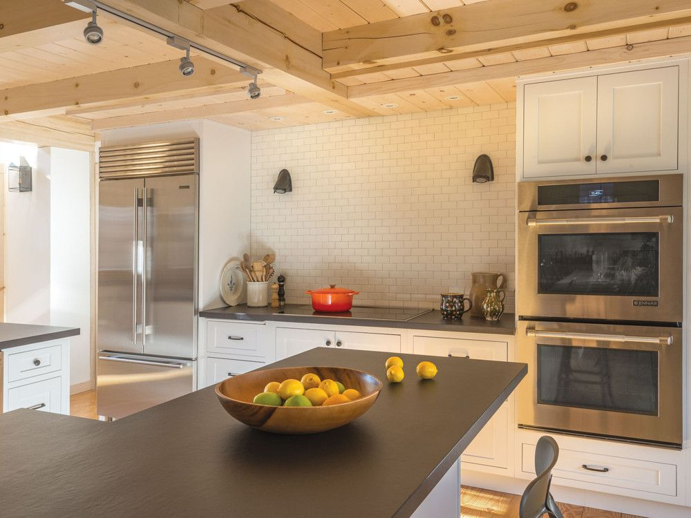 Durable countertops of Dekton by Cosentino—a new, engineered-stone product that's almost indestructible—makes for ease of use, as do a Kohler stainless-steel farmhouse sink, Sub-Zero refrigerator, and Jenn-Air oven and induction cook top. White subway tiles from Ann Sacks provide a satisfying backdrop.