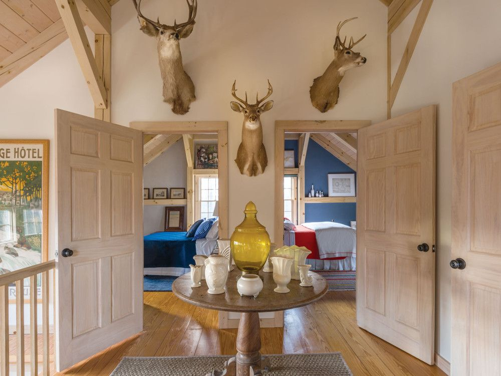 The deer heads above the entrance to the guest bedrooms were purchased at an antique shop in nearby Hudson, New York. The hall table is filled with a trove of the owners' finds, including pieces of McCoy pottery and a Moroccan glass lantern.