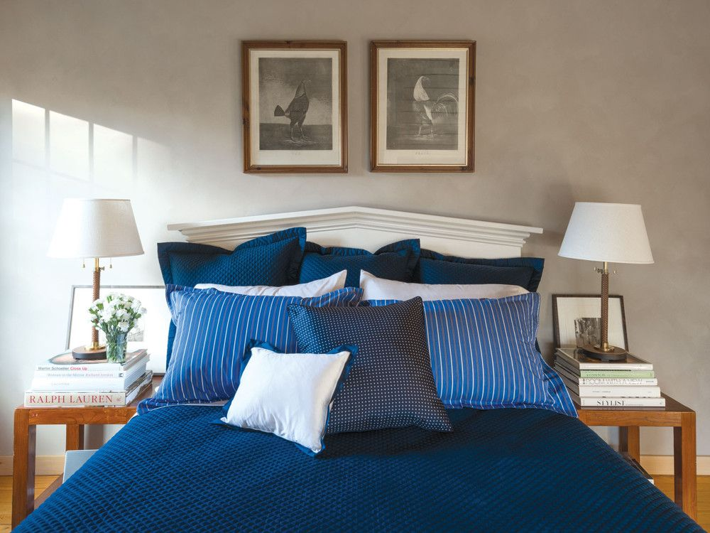 For this guest bedroom, designer McAvoy explained that the decorating was analogous to finding accessories for a suit, dressing the bed in layers of contrasting blue patterns from Ralph Lauren. On the walls, Ralph Lauren Paint's