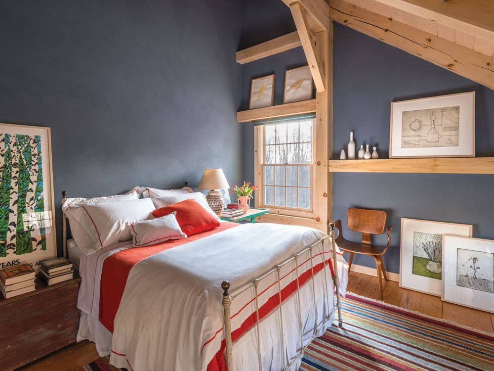 The other guest bedroom, with exposed woodwork that shows off mortise-and-tenon joinery, is filled with paintings from the owners' collection. The walls are covered in