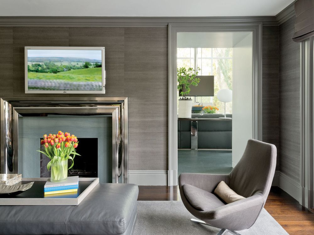 Donghia grasscloth brings organic warmth to a polished steel mantel. Next to it, a Metropolitan swivel chair from B&B Italia.