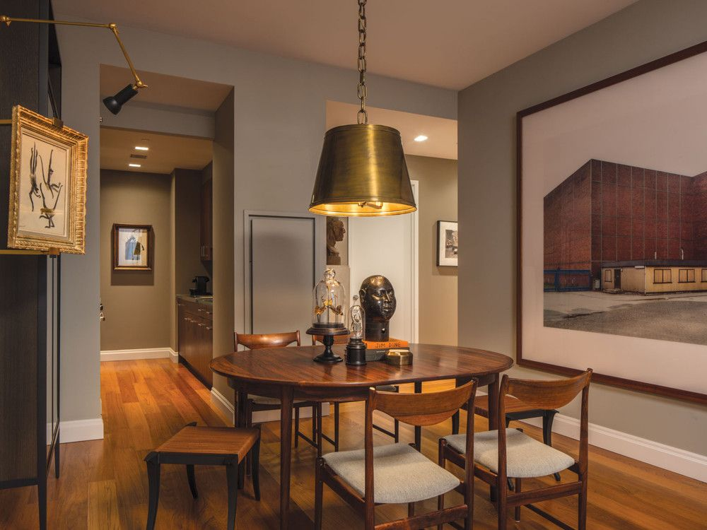 In the dining room, Luis Bustamante's chandelier crowns the client's 1960s Danish dining set. The African bronze head is from Etos.