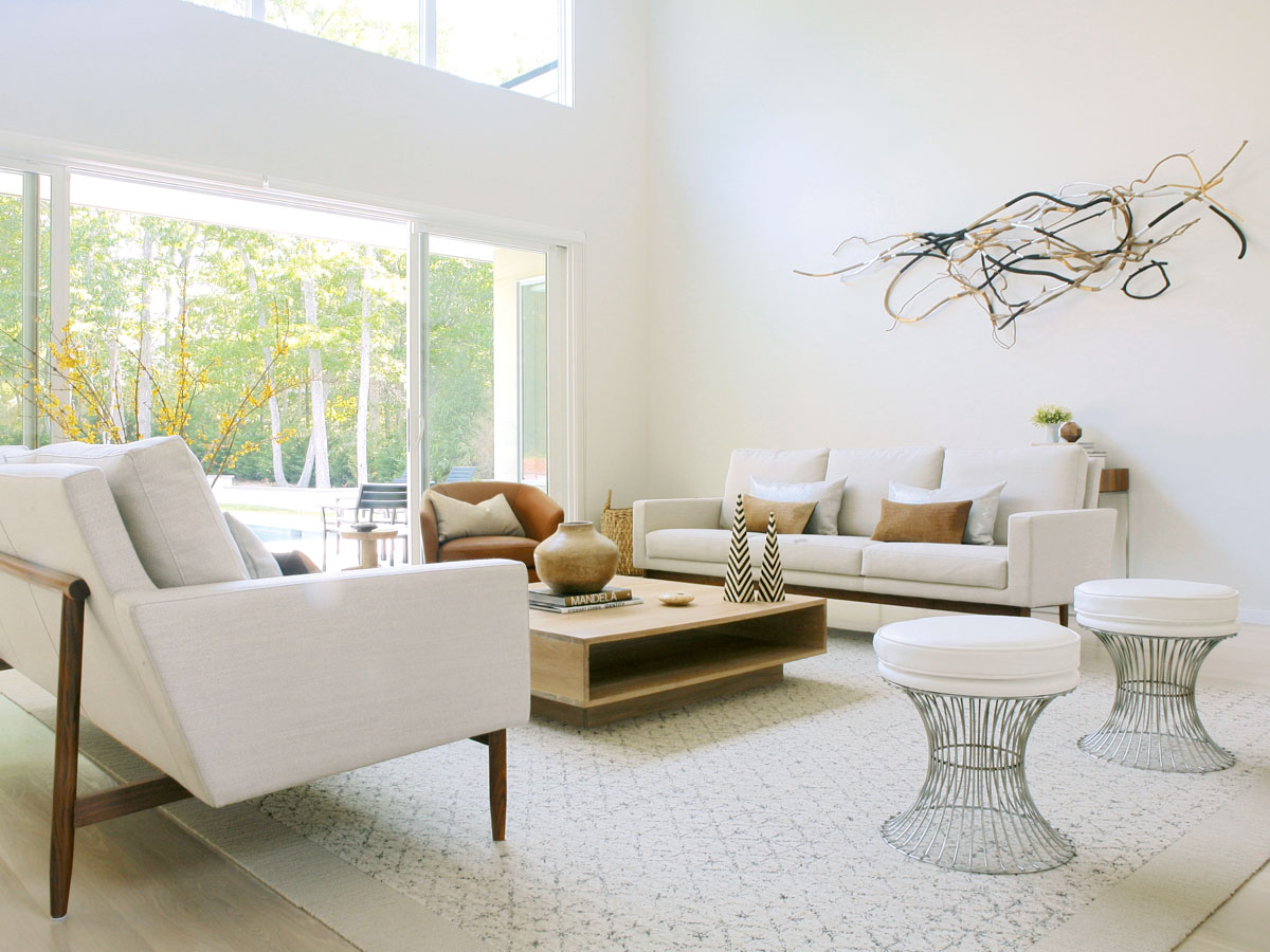 The living room was designed to feel like an extension of the outdoors. A custom wood coffee table, a beautiful leather swivel chair, cowhide and linen pillows, and an abstract wooden wall sculpture commissioned from artist Christina Watka instill an organic, natural feel.
