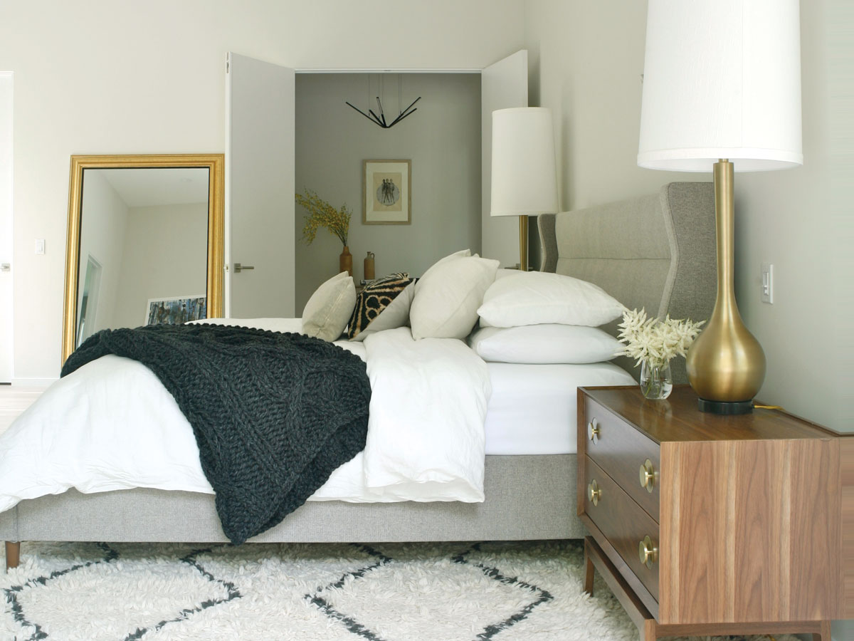A wing bed from Gus Modern, elongated Global Views table lamps, and wide midcentury-inspired night stands are in proportion to the extra-large master bedroom.