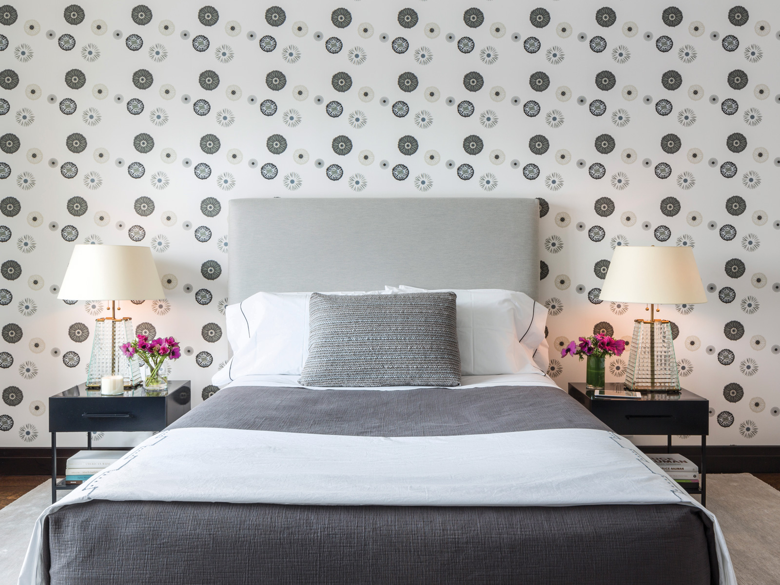 Story's own Kimono wallcovering in a guest bedroom make inexpensive bedside tables from CB2 (refinished in black laquer) pop. Robert Altman lamps and linens by Anichini and Julia B deliver the luxe elements.