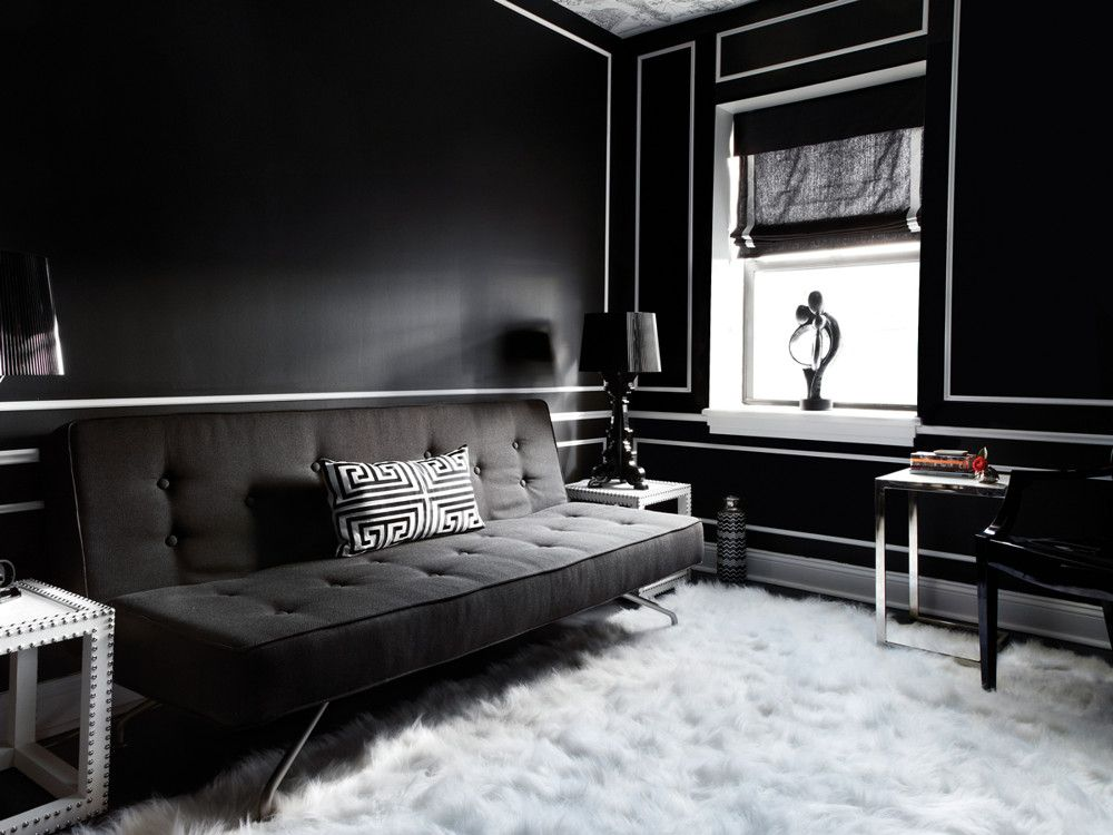 The black-and-white guest room is furnished with a lively assortment of varied textures and striking forms. The deeply textured wool flokati, which the clients brought with them to their new digs, provides high contrast to the sleek, metal-legged sofa from BoConcept and nail-head-trimmed end tables from Bungalow 5. The clients' own modern curvilinear sculpture on the windowsill and the riff on classical curves of the black plastic lamps from Kartell soften the room's sharp geometries.