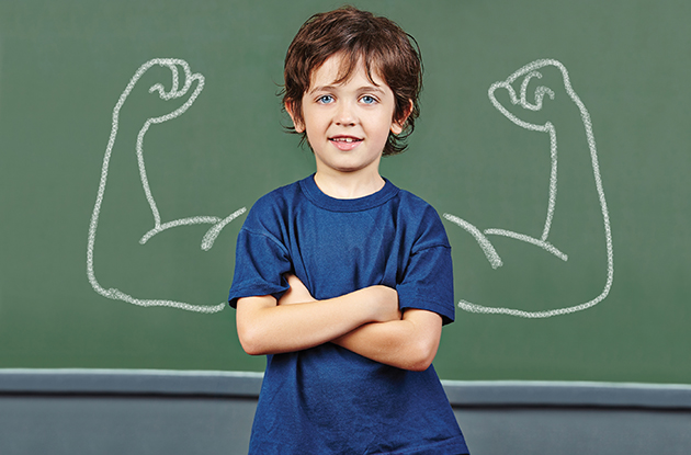 child with muscles drawn on blackboard behind him