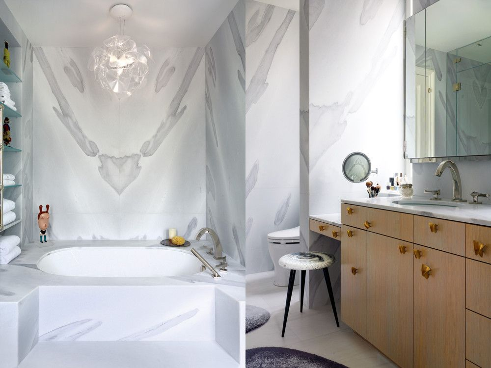 Left: Custom tub nook in the master bathroom, which is lined in slabs of book-matched marble. Right: Ted Muehling's Butterfly pulls alight on the bath's custom vanity.