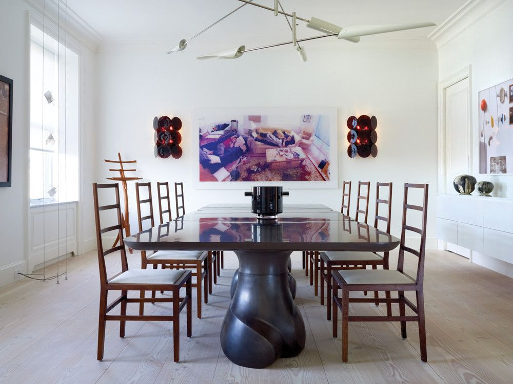 In the dining room, three square tables by Eric Schmitt align to create one large dining table. A slim four-tier Sarus Chandelier by David Weeks counters the tables' cast-bronze sculptural base. Vintage Seguso three-disc sconces from Todd Merrill frame a large photograph by Barry Frydlender on the back wall.