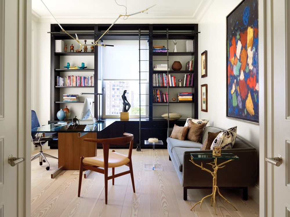In the library, an Archipenko bronze figure watches over the city below, while an LED chandelier by Lindsey Adelman drapes delicately in dialogue with the bronze branch legs of the Holly Hunt side table. Vladimir Kagan glass extendable desk is from Ralph Pucci; vintage teak Bullhorn Chair is by Hans Wegner from Wyeth.