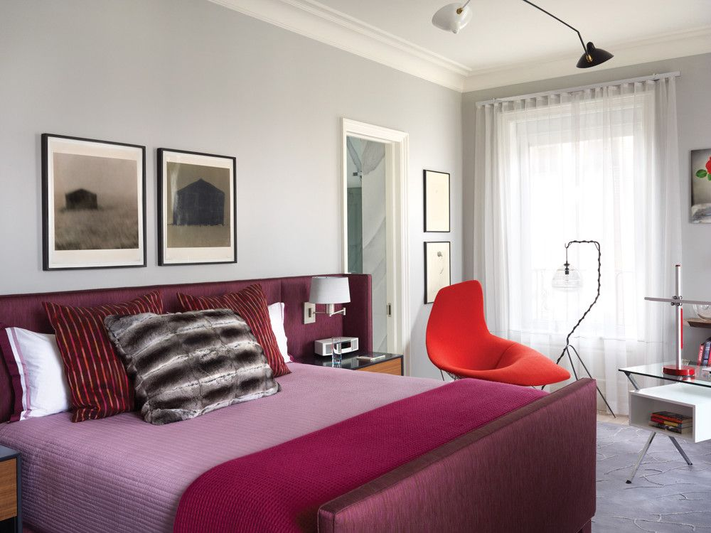 A custom bed sports a purple throw from ABC Carpet & Home. On the Bertoia chaise is a red boucle fabric.