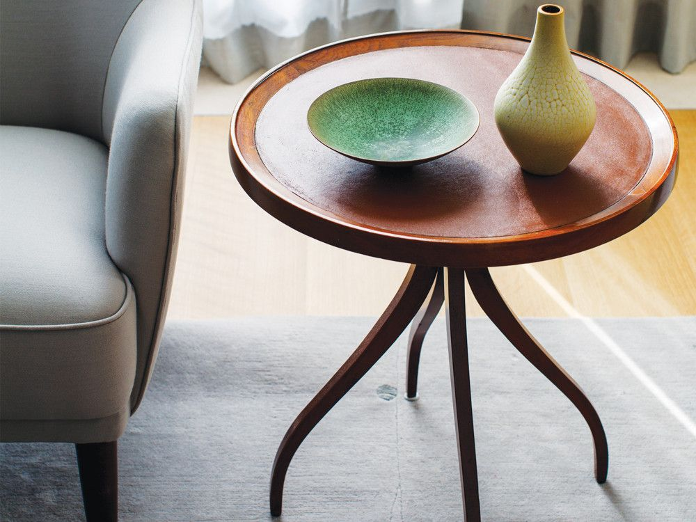 A vintage walnut table with a leather insert was purchased from Thomas Hayes, a Los Angeles dealer.