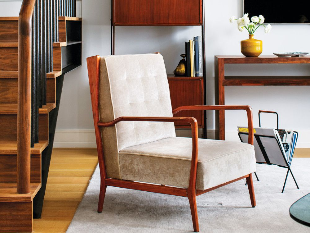 n a corner by the stairs, a '60s armchair from Espasso keeps company with a Jacques Adnet magazine stand. The '60s Italian bookcase and a console from BDDW stand guard behind them.