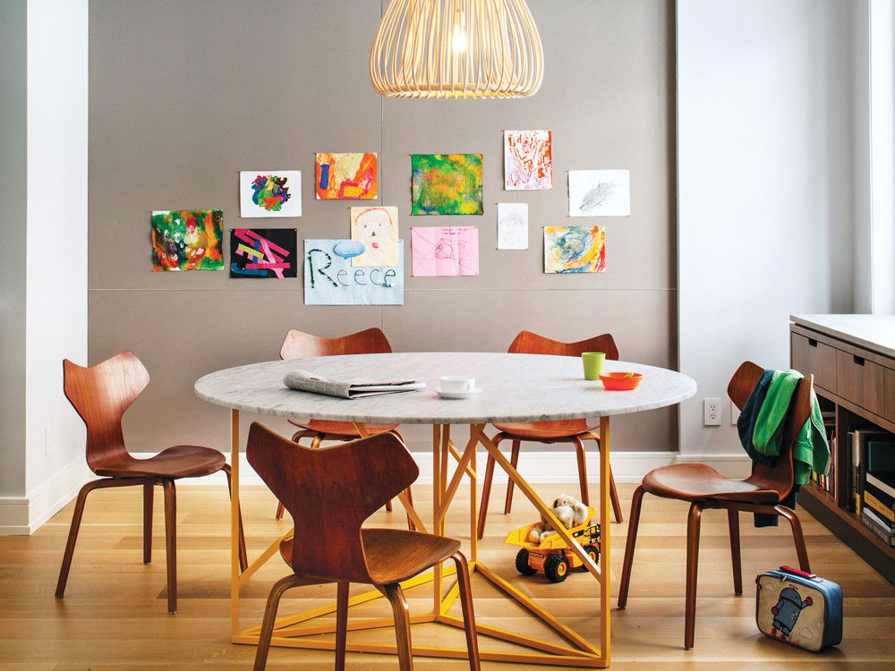 In the family dining area, the children's drawings provide the artwork. The round table with its playful, bright yellow base is by American architect Robert Bristow. It is circled by vintage Grand Prix chairs, designed by Arne Jacobsen, and illuminated by an Orbita pendant from Bonacina Vittorio.