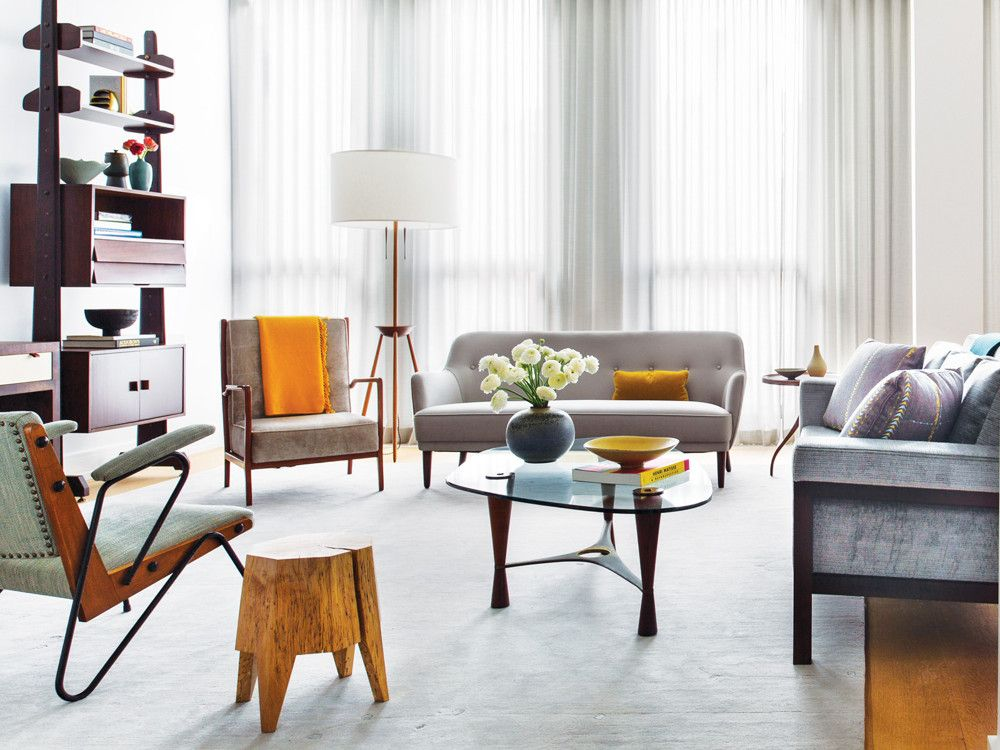 An artful blend of old and new pieces of furniture and a soothing color palette fill the living and dining areas. An of-the-moment Christophe Delcourt sofa in the room's center contrasts with the vintage chair by Brazilian architect Lina Bo Bardi on the left.