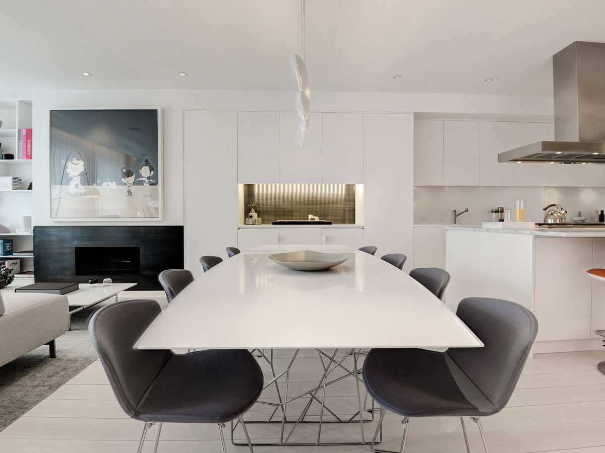 In the dining area, Bertoia chairs from Knoll cozy up to a Synapsis table from Porro at West NYC Home.