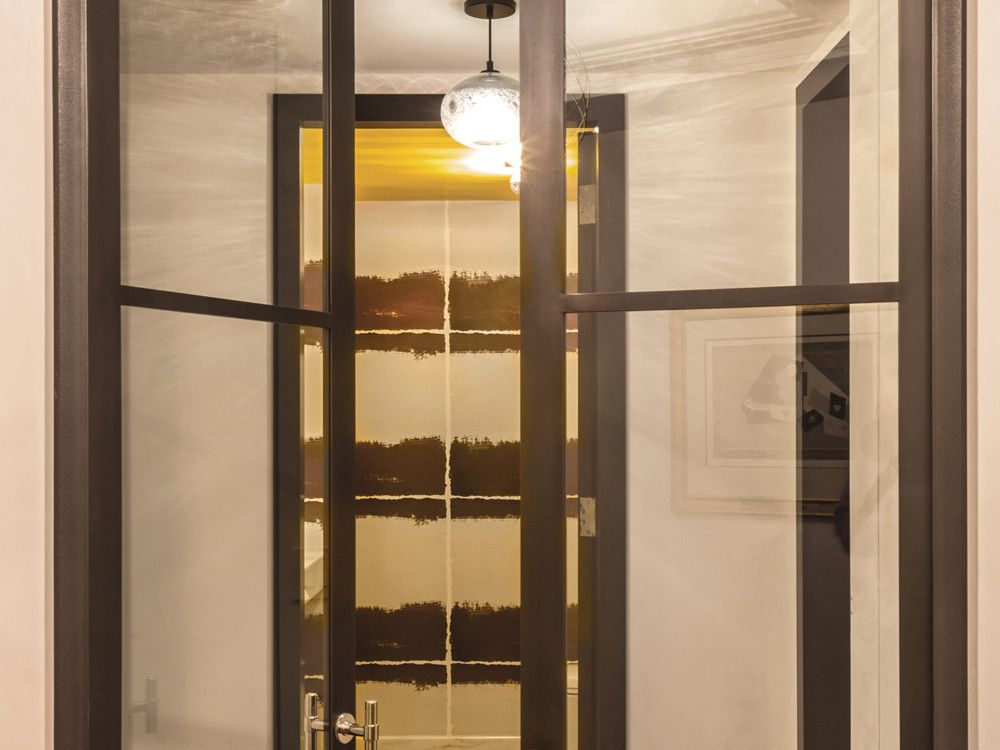Darren Vigilant's steel doors lead to a powder room papered in Elitis wallcovering.
