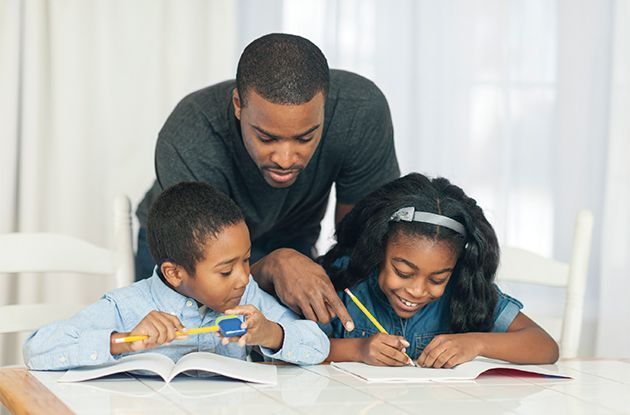 father and children doing homework