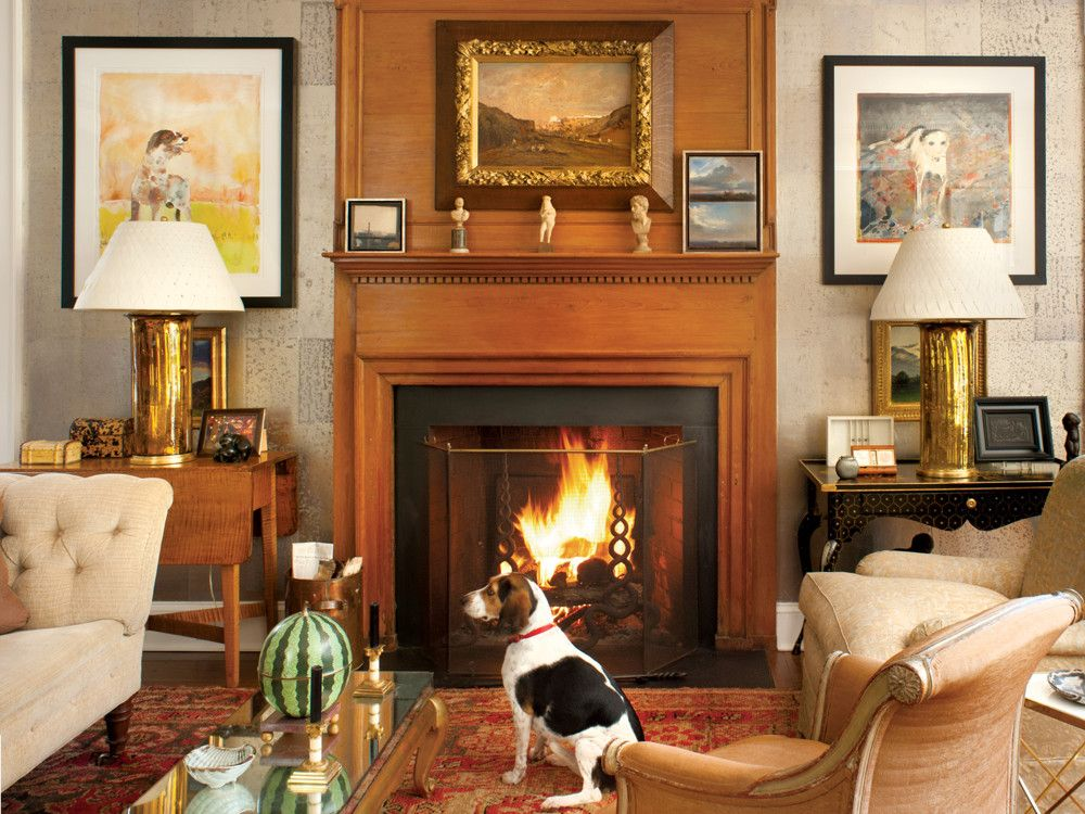 Flanking the fireplace are two dog paintings by Robert Andrew Parker; the little mirrored-top coffee table is Jansen and the andirons, purchased in LA, are by Tony Duquette, purportedly for the Warner Estate.