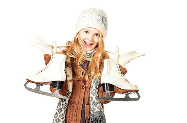 young girl holding ice skates