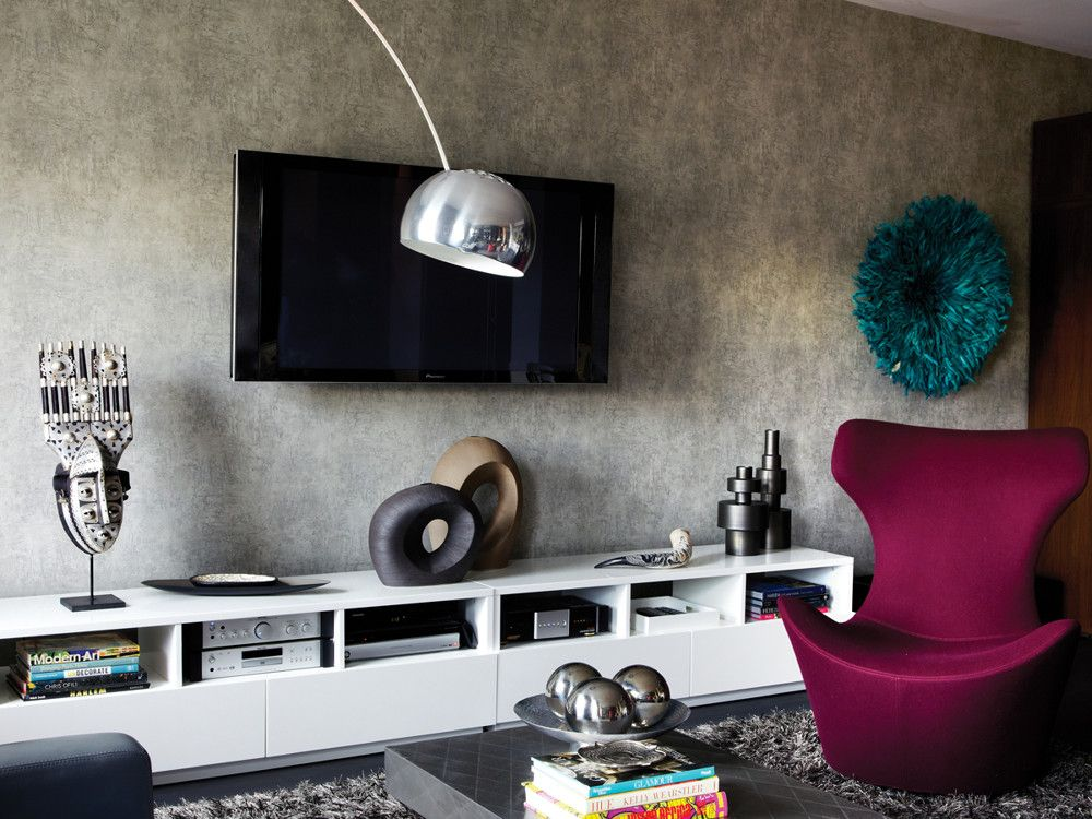 In the living room, an updated wing chair fronts the low-slung credenza; textured wallpaper is from Sonia's Place.