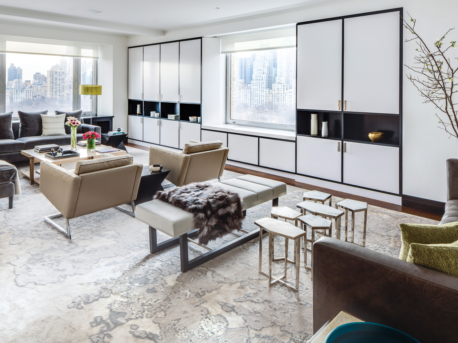 The complex layering of this deceptively simple living room offers myriad tactile and visual contrasts: white lacquer cabinetry with ebonized wood display niches; polished materials such as the legs of 1970s cantilevered Milo Baughman armchairs from Oliver Modern set against soft Romo linen upholstery; and a plush silver fox throw from Dualoy complementing a settee in supple Moore & Giles leather.