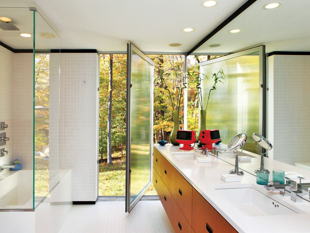 he pair installed pivoting doors of ribbed glass in the master bath; topping the new teak cabinetry is bright white Silestone.