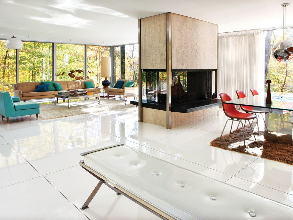 The freestanding travertine-and-steel fireplace dividing the living and dining areas sealed the deal for Mandolene and Goddard. The couple furnished the place with period pieces collected over two decades. The living room's Paul McCobb sectional has its original fabric. The Milo Baughman coffee table dates to the late '60s. The floor is newly poured, radiant-heated concrete finished with commercial-grade high-gloss epoxy.