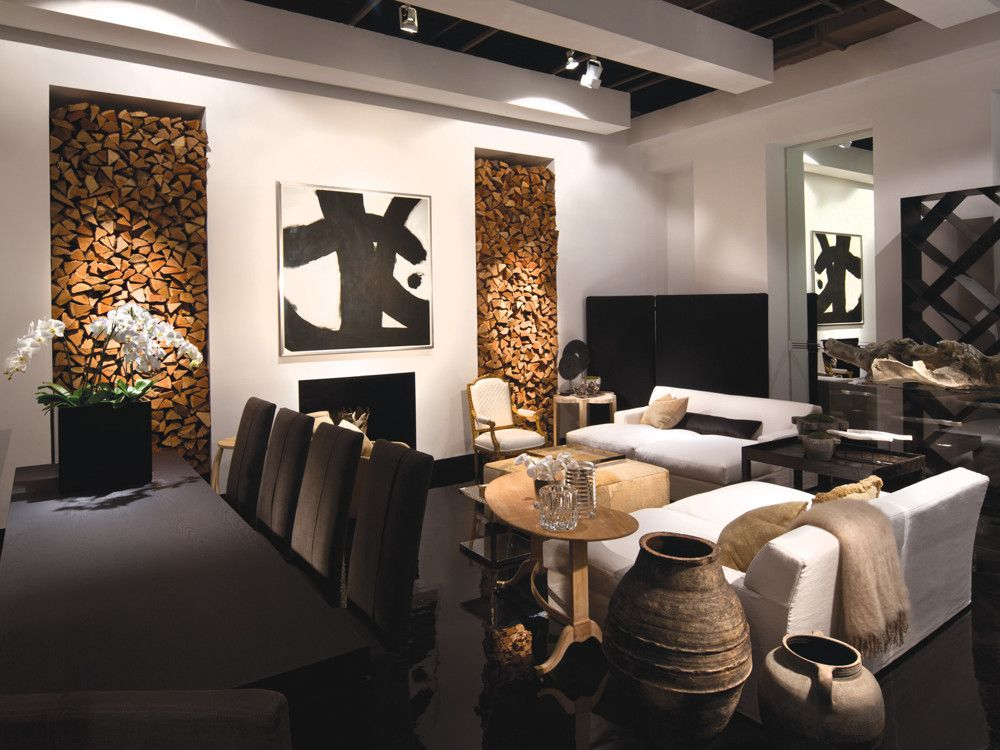 In a subtle palette of white, gray, brown, and black, the artful space gets added impact from its black polyurethane floor. The painting over the mantel is a collaboration between Caitlin Dinkins and Minh Nguyen. Sofas from Italian manufacturer Meridiani provide relaxed-yet-stylish seating. The overscale dining table, an import from Belgium, is flanked by dining chairs of Dawkins' own design.