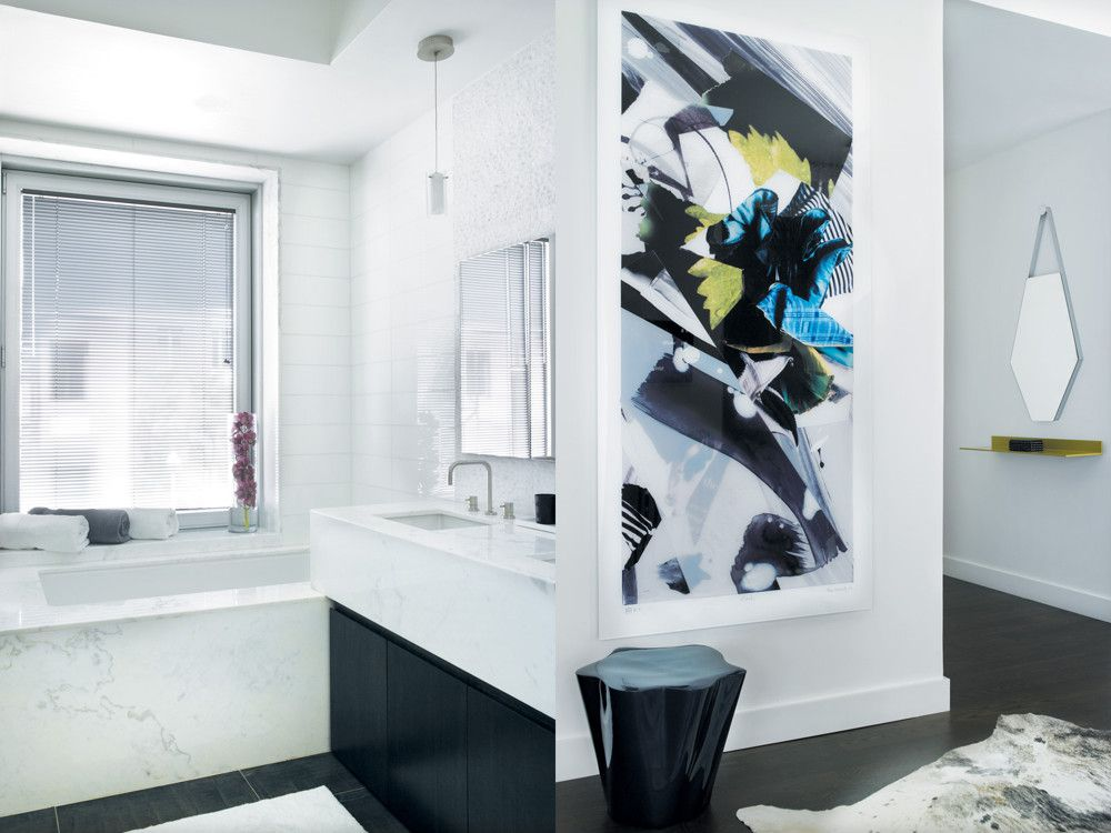 "Left: For increased function, Hassan modified the vanity unit in the master bath with pullout drawers and cut outs around the plumbing. Right: With Ligne Roset's Mon Beau mirror and DDC's EOS shelf, the entry hall sets a stylish tone for the rest of the interior. In the living room, an art wall displays Tiboli, a 7-ft.-high collage by artist Lisa Fromartz. Beneath it is a blue stool called ""By the Trees,"" which introduces an organic element of surprise into the strict modern mix."