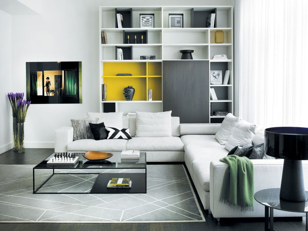 In the living room, Hassan used clean, crisp, modern furnishings in a restrained palette with a few pops of color for focus. The bookcase from Molteni & C camouflages 