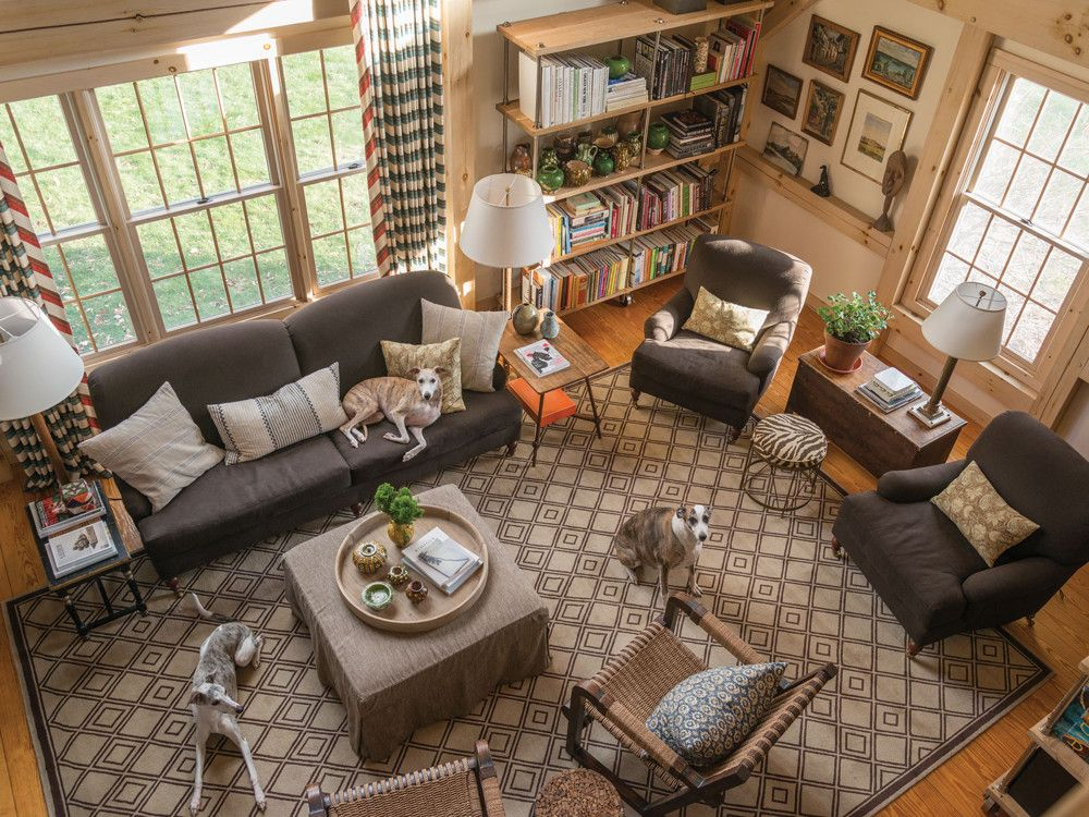 The double-height living room is dressed in soft shades of brown with a mix of furnishings that range from classic Brunschwig & Fils easy chairs and sofa to rustic rope chairs and bookcases from Ralph Lauren. The couple found the striped zebra stool at a roadside antiques shop. Lining the walls are landscape paintings that one of the owners has collected since his college days, as well as paintings by Daniel Charles Feldman.