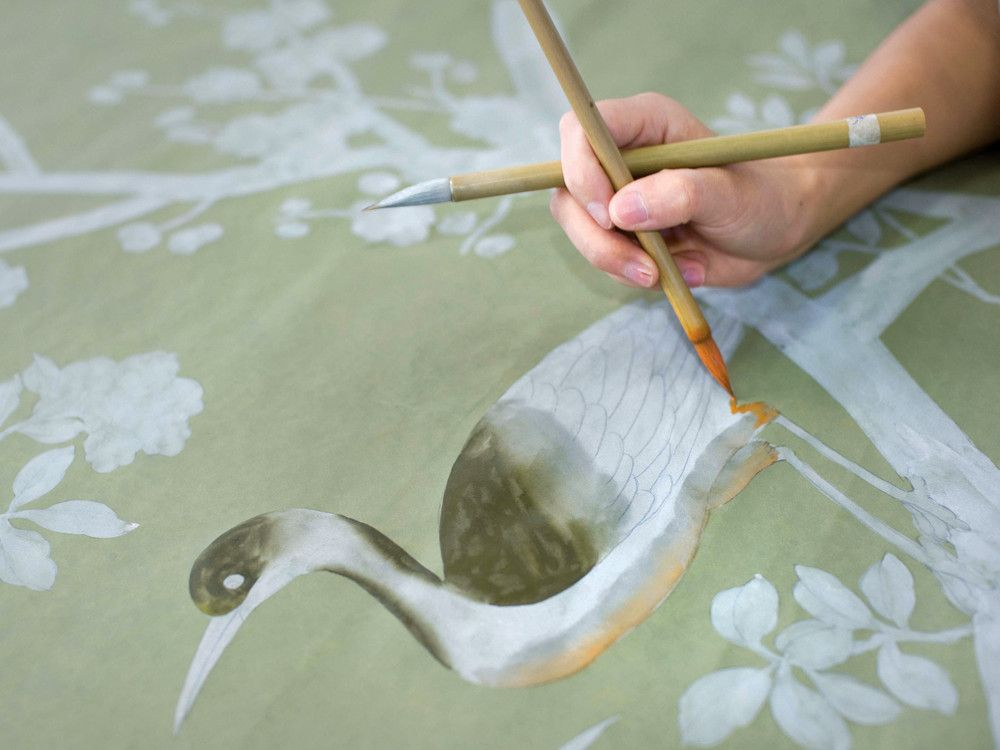 The expertise of the firm's Chinese artisans is unparalleled. Here, the hands of an artist painting on silk, applying detail oh-so precisely over an under layer while the pencil outline remains visible.
