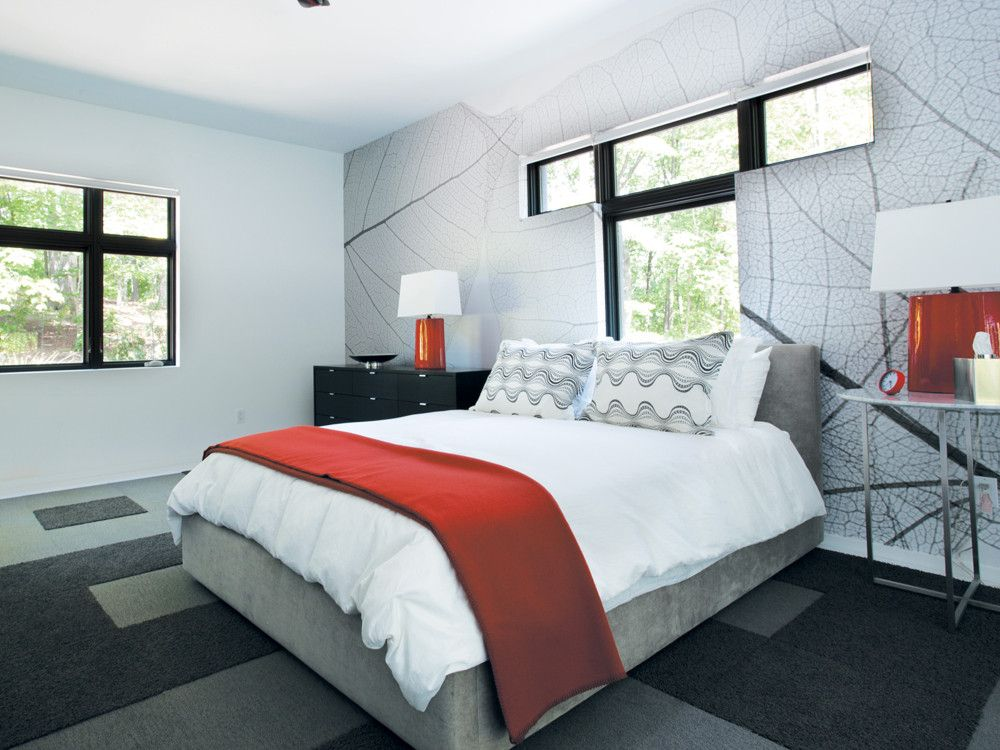 One of the guest rooms sports a persimmon and gray palette; a custom super-graphic print of a eucalyptus leaf from Murals Your Way covers the wall behind the bed.