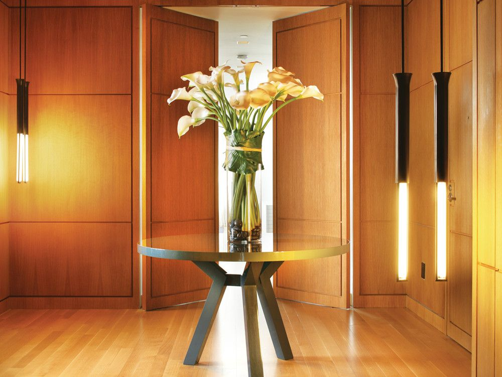 In the hallway/entrance, Theis created a warm enclave with white oak floors and custom-designed wall panels. The lacquered top of the Christophe Delcourt-designed table from Ralph Pucci introduces a bit of sheen. The hanging lights are by Michael Anastassiades.