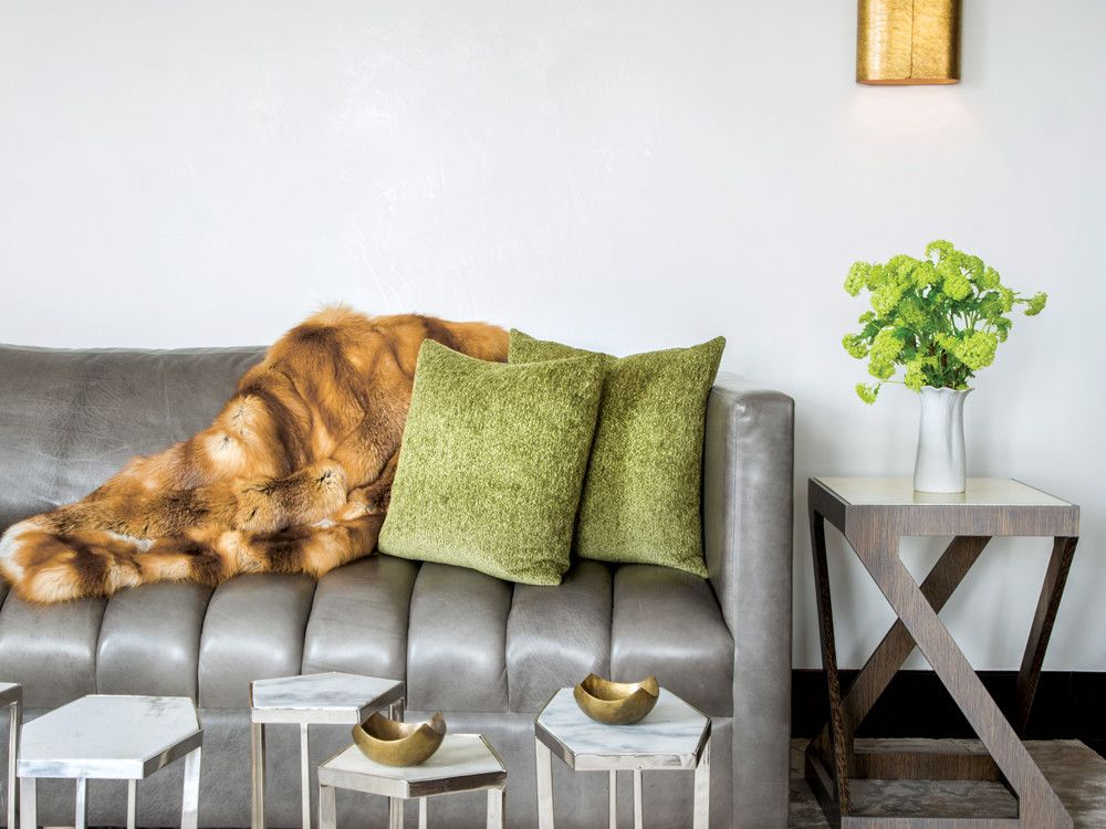 "orta Romana sconces, a Mecox Gardens ""puzzle"" table, and a Dualoy fox throw add lavish touches to a leather sofa fabricated by Furniture Masters. The 1940s side table is from Arlene Angard Designs."